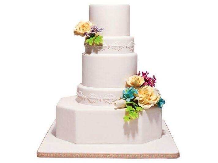 Elegant white wedding cake with colorful fresh flowers