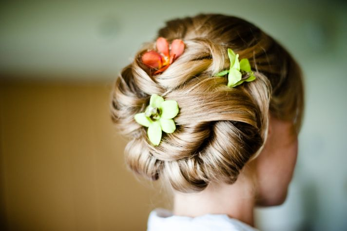 Tropical wedding flowers adorn outdoor wedding ceremony arbor