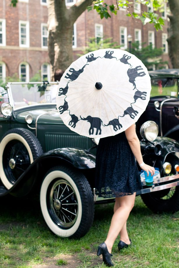Vintage wedding day transportation and chic wedding guest with custom parasol