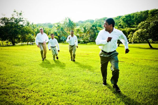Groom and groomsmen run to wedding ceremony