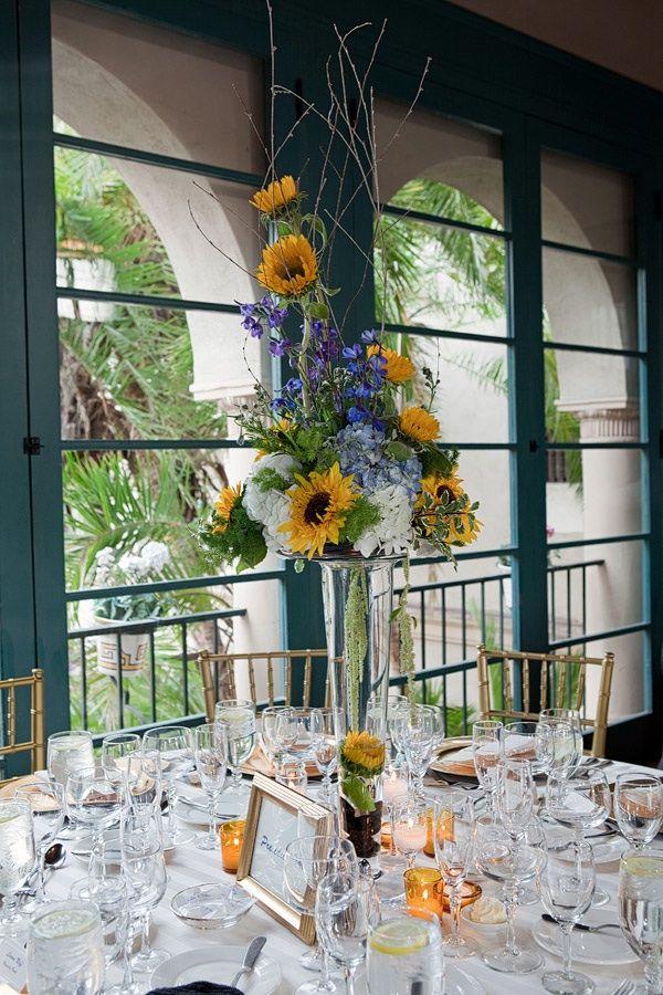 Rustic chic wedding reception centerpiece featuring sunflowers and hydrangeas