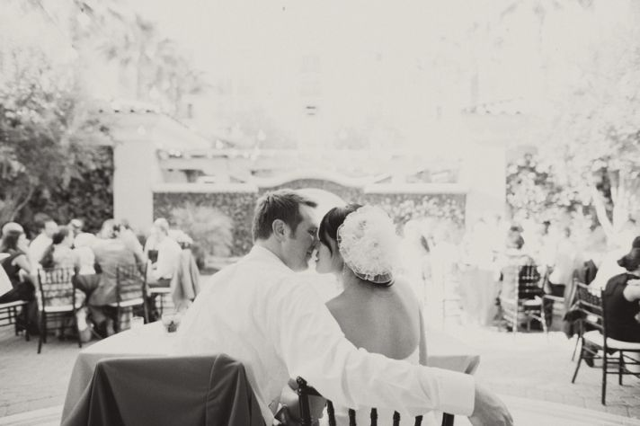 Happy bride and groom kiss at outdoor wedding reception