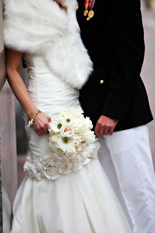 Bride wears mermaid wedding dress, fur bridal shrug, poses with military groom