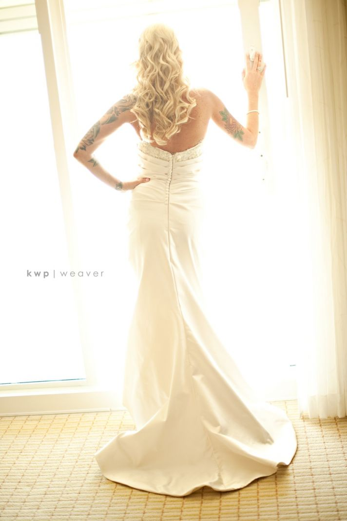 Edgy bride wears ivory mermaid wedding dress, all-down wedding hairstyle