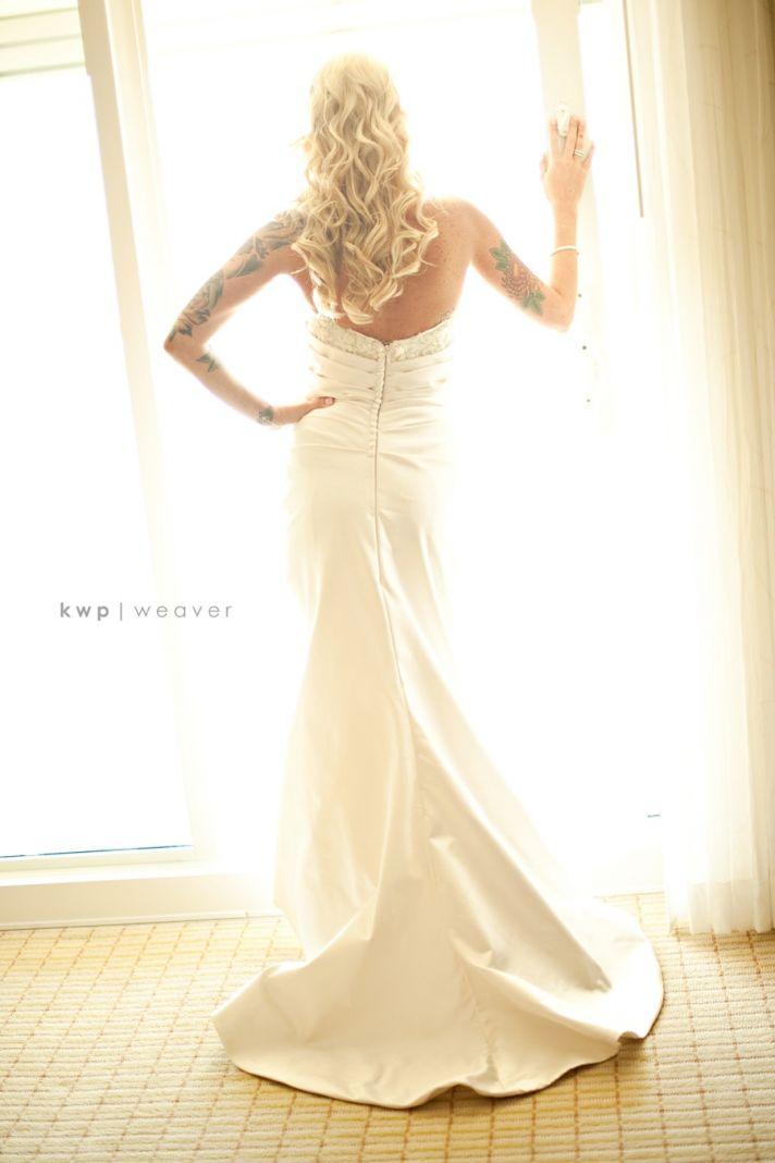Edgy bride wears ivory mermaid wedding dress, all-down wedding hairstyle