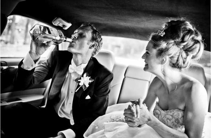 Bride-groom-drink-in-limo-while-heading-to-wedding-reception