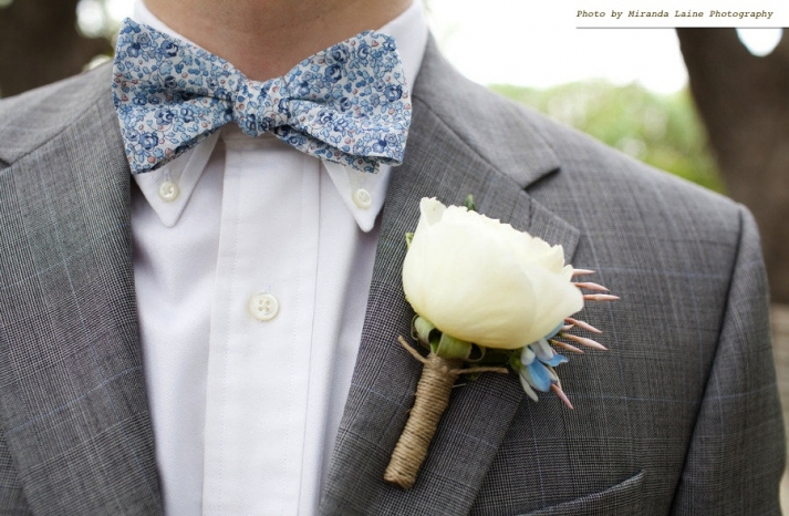 Groom-wears-blue-bow-tie-floral-print-grey-tailored-suit