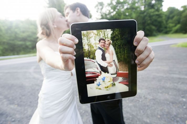 bride groom kiss with wedding photo on ipad