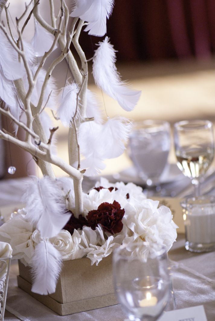 Whimsical wedding centerpieces with branches feathers roses carnations