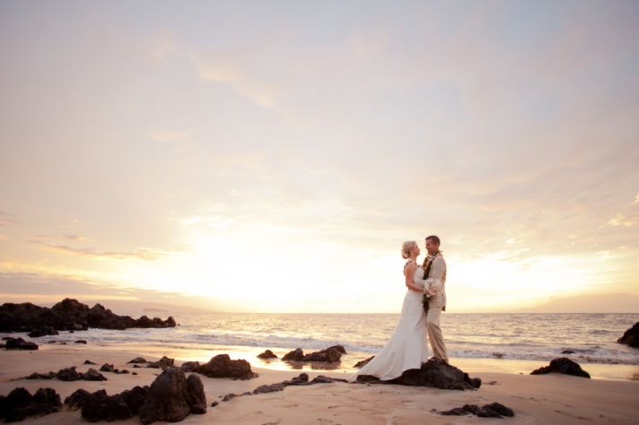 beach bride and groom watch the sun set