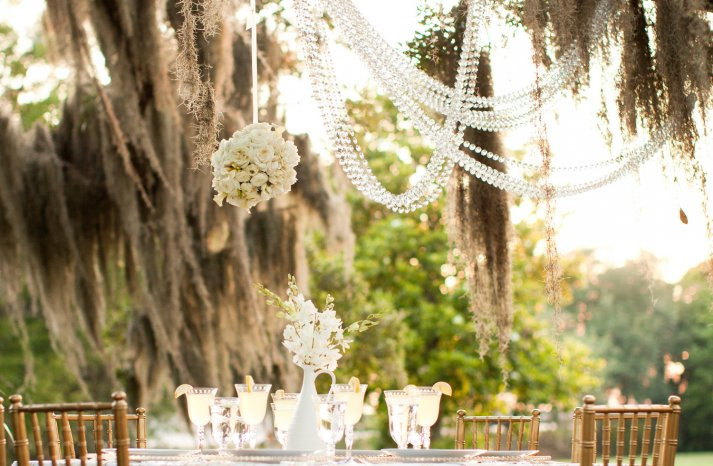 Outdoor wedding reception under a tree draped in crystals