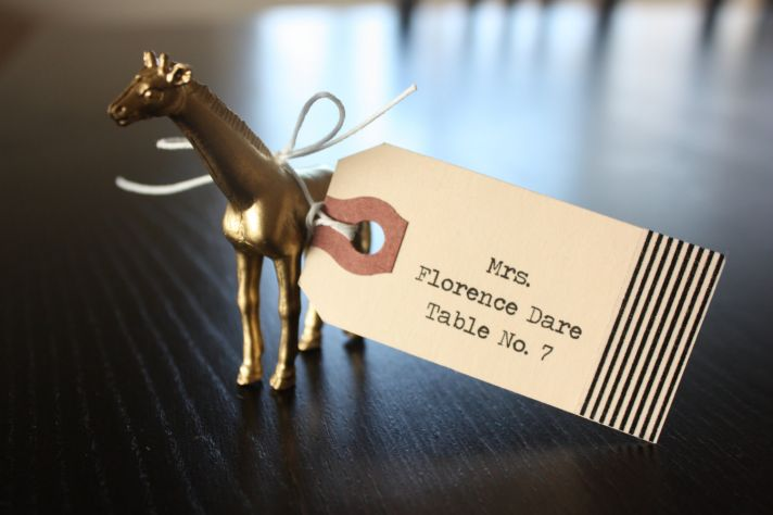 Vintage style wedding escort card attached to gold mini horse