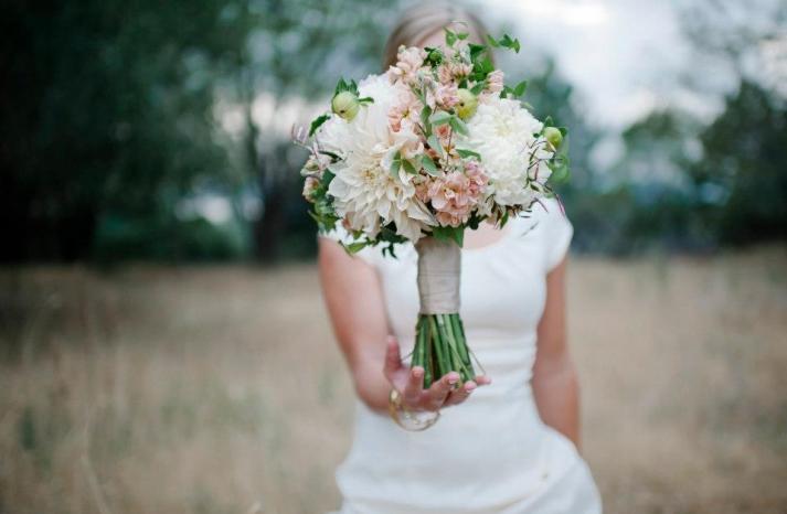 Bride balances romantic fall wedding bouquet with ivory dahlias