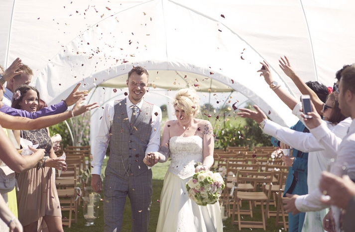 groom wears checkered charcoal gray vest and slacks with white shirt