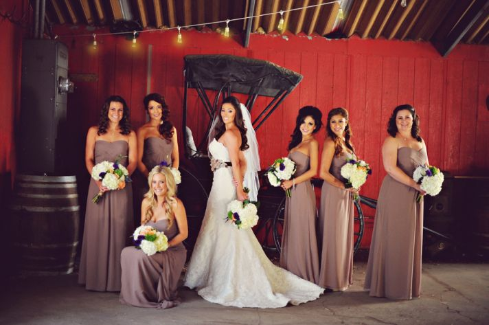 Bridesmaids posing in front of antique buggy