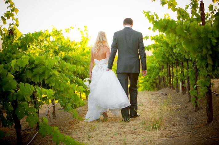 Real bride and groom walk in the vineyard