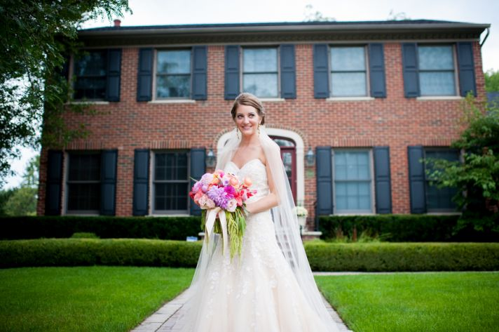 Bride in front of brick mansion