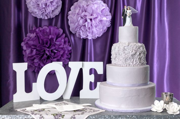 White wedding cake from from Magnolia Bakery with a purple backdrop
