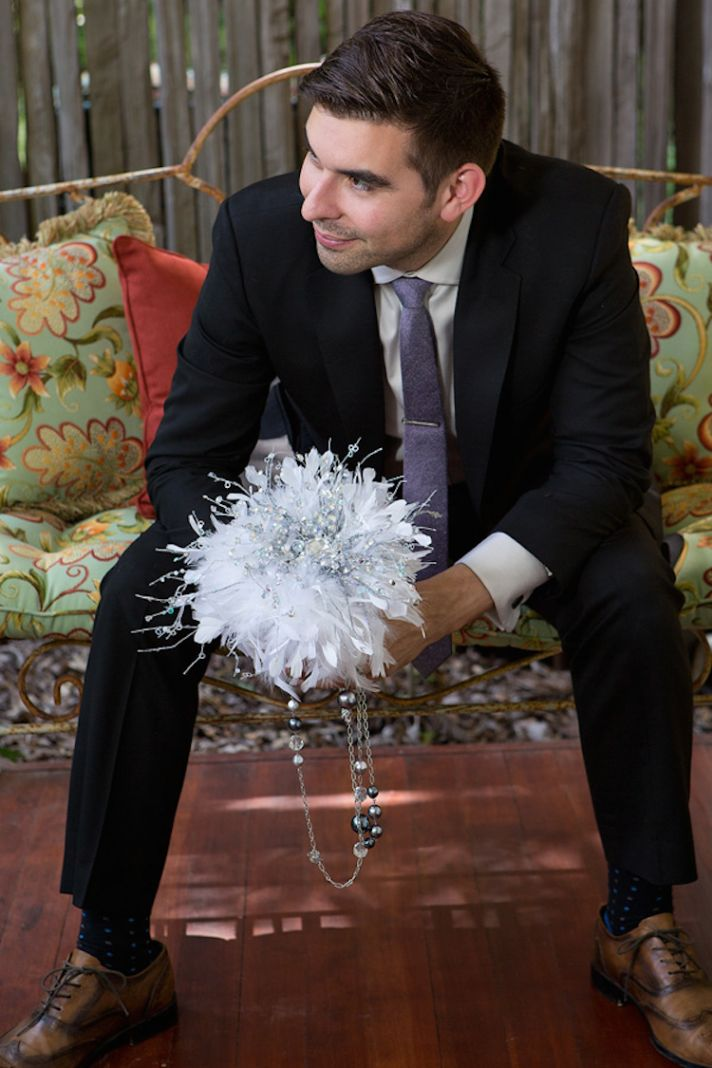 Groom with white feather bouquet